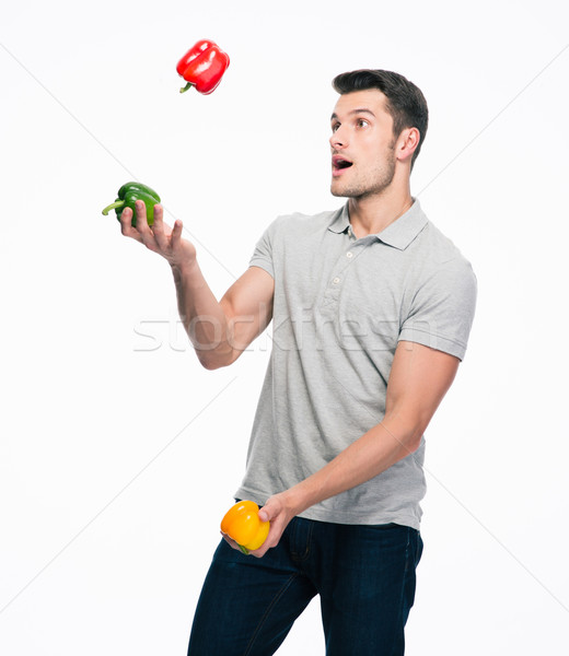Happy young man juggling pepper Stock photo © deandrobot