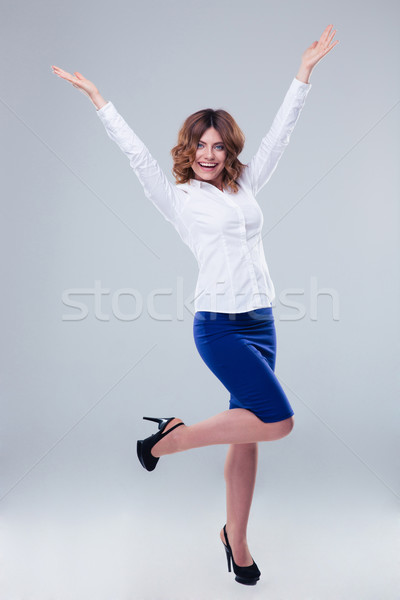 Happy woman with raised hands up Stock photo © deandrobot