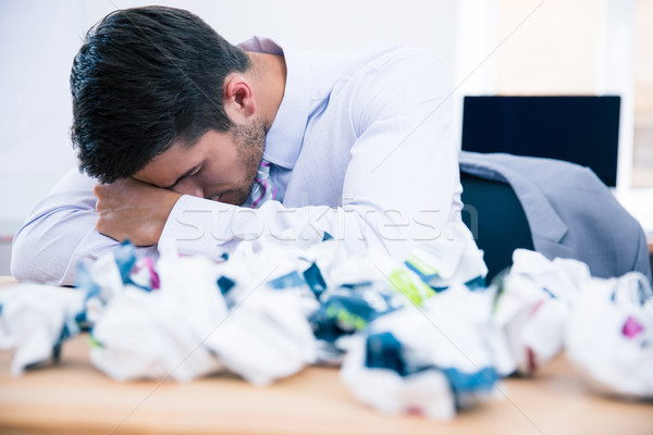 Tired businessman sitting at the table in office Stock photo © deandrobot