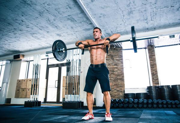 Muscular man lifting barbell Stock photo © deandrobot