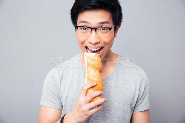 Asian uomo mordere pane grigio occhiali Foto d'archivio © deandrobot