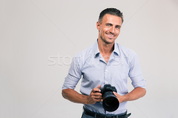 Smiling photographer holding camera Stock photo © deandrobot