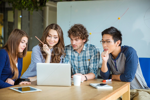 Group of students using laptop together Stock photo © deandrobot
