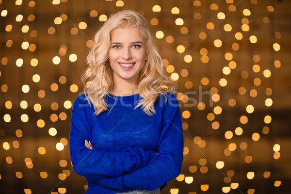 Smiling woman standing over holidays lights background Stock photo © deandrobot
