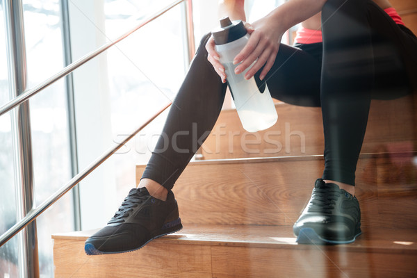 Legs of attractive woman athlete sitting on stairs in gym Stock photo © deandrobot
