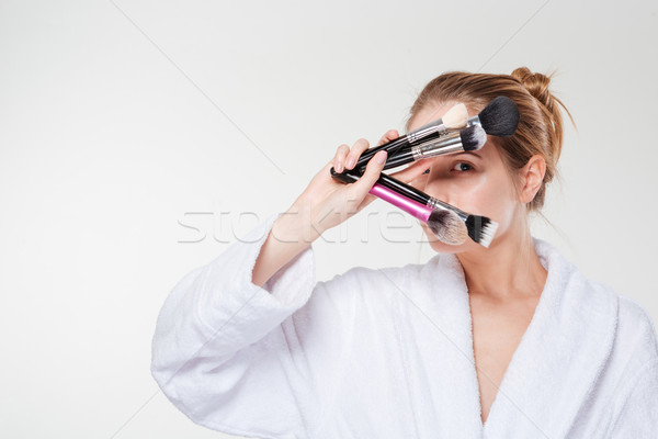 Woman in bathrobe holding makeup brushes Stock photo © deandrobot