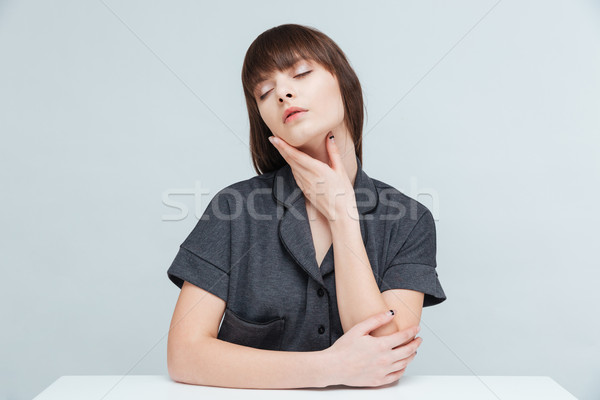 Relaxed woman sitting at the table with closed eyes Stock photo © deandrobot