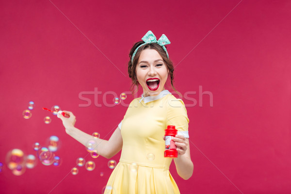 Cheerful pretty young woman having fun with soap bubbles Stock photo © deandrobot