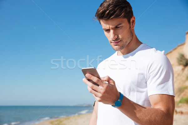 Sportsman using fitness tracker and smartphone outdoors Stock photo © deandrobot