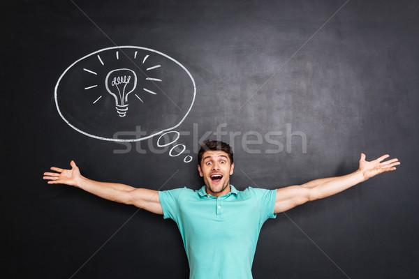 Feliz excitado joven las manos en alto idea pizarra Foto stock © deandrobot