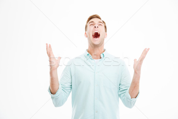 Mad furious businessman with raised hands shouting and looking up Stock photo © deandrobot