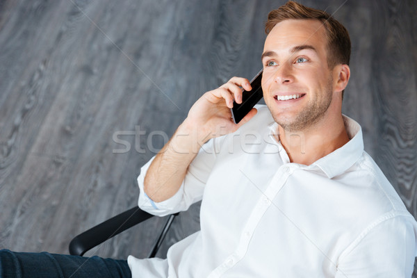 Smiling young businessman talking on mobile phone in office Stock photo © deandrobot
