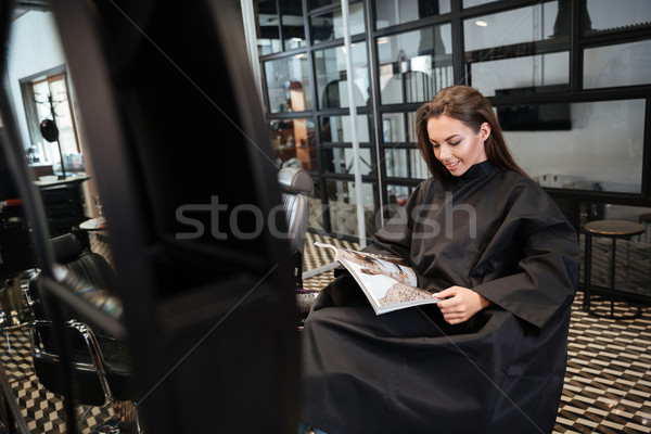 Woman sitting in beauty salon and reading fashion magazine Stock photo © deandrobot