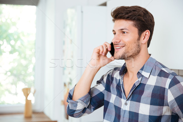 Smiling handsome young man talking on mobile phone at home Stock photo © deandrobot