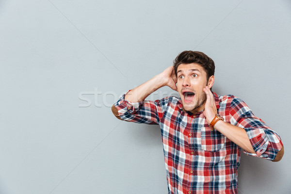 Stunned afraid young man in checkered shirt standing and shouting Stock photo © deandrobot