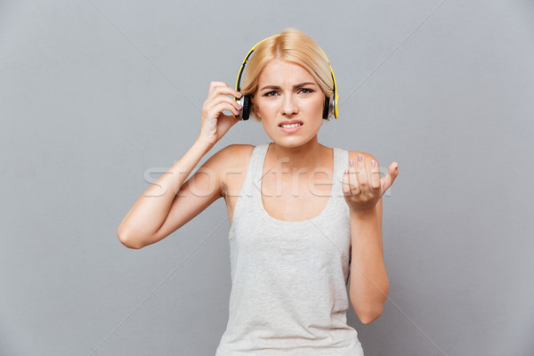 Frowning irritated young woman taking off headphones Stock photo © deandrobot