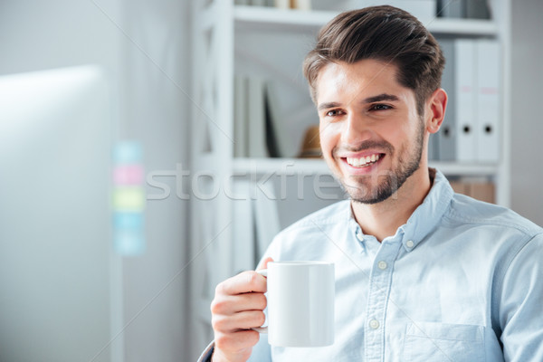 Close-up portrait of a businessman with cup in office Stock photo © deandrobot