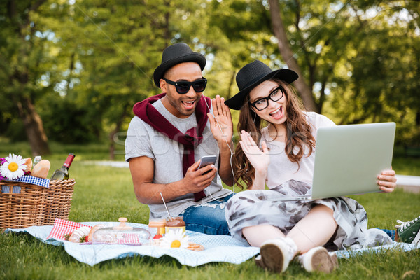 Couple with laptop listening to music from smartphone in park Stock photo © deandrobot