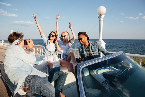 Group of cheerful people driving and having fun in cabriolet Stock photo © deandrobot