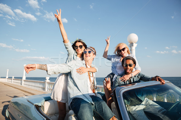 Smiling friends driving car near the sea and having fun Stock photo © deandrobot