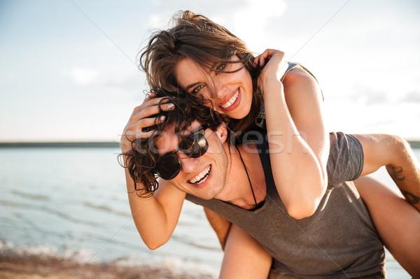 Férfi háton barátnő óceán fiatal mosolyog Stock fotó © deandrobot