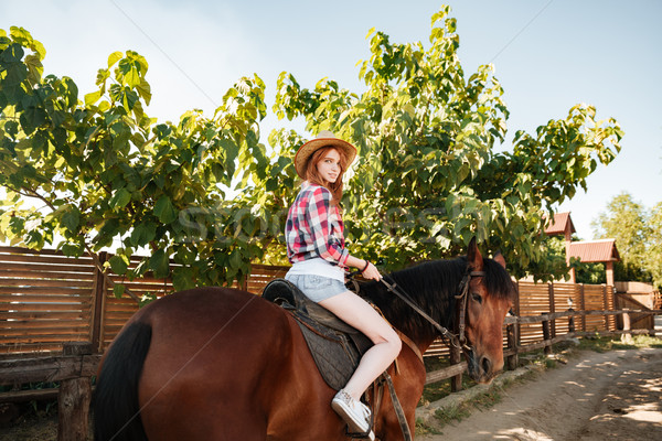 Beautiful redhead young woman cowgirl riding horse in village Stock photo © deandrobot