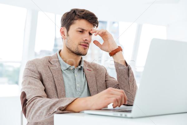 Pensativo jóvenes empresario de trabajo portátil Foto stock © deandrobot