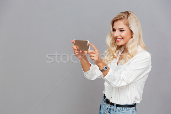 Beautiful young girl making photo on smartphone Stock photo © deandrobot