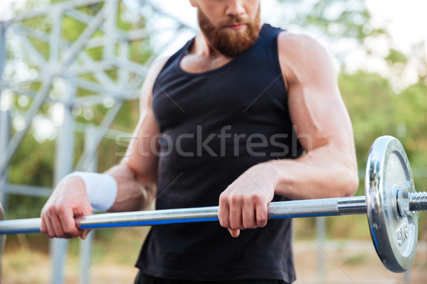 Cropped image of a serious young bearded man athlete exercising Stock photo © deandrobot