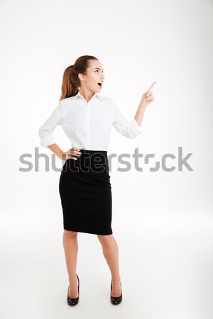 Stock photo: Cheerful young businesswoman pointing finger away
