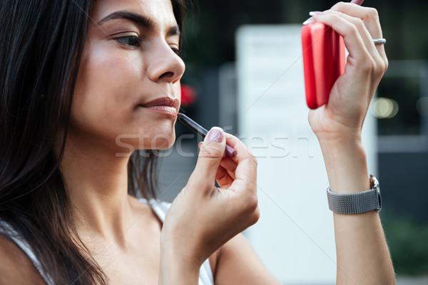 Donna guardando specchio rossetto esterna Foto d'archivio © deandrobot
