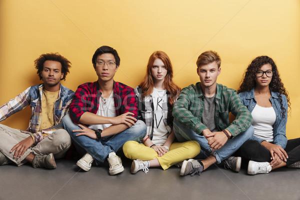 Groupe sérieux jeunes séance jambes croisées Photo stock © deandrobot