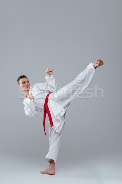 Sportoló kimonó gyakorlat karate fiatal izolált Stock fotó © deandrobot