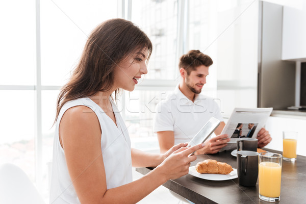 Woman having breakfast and using tablet while boyfriend reading newspaper Stock photo © deandrobot