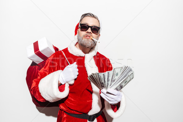 Man santa claus with gift sack smoking and holding money Stock photo © deandrobot
