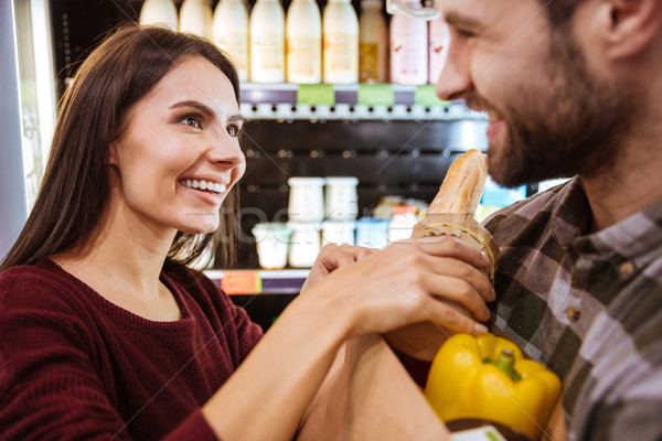 Couple with packet of food doing shopping in grocery shop Stock photo © deandrobot