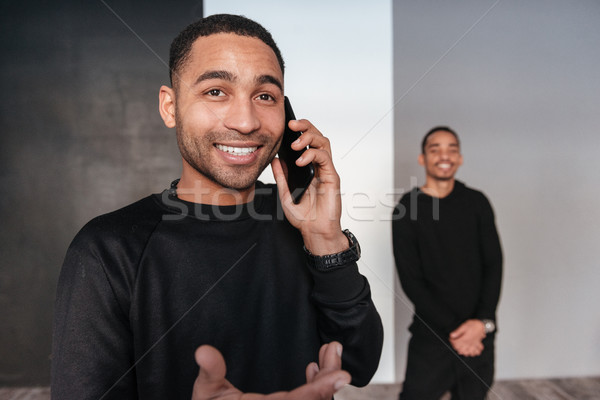 Cheerful african young man stading and talking on mobile phone Stock photo © deandrobot