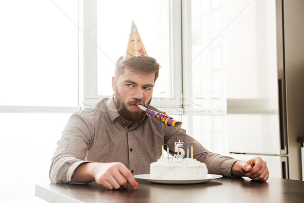 Angry bearded father of birtday little boy sitting in kitchen Stock photo © deandrobot