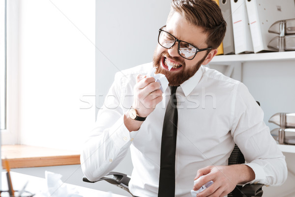 Angry businessman sitting in office and tears paper with teeth Stock photo © deandrobot