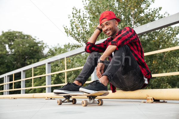 Cheerful dark skinned man sitting with his skateboard Stock photo © deandrobot