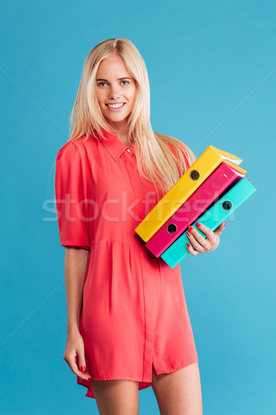 Young happy woman holding colorful binders Stock photo © deandrobot