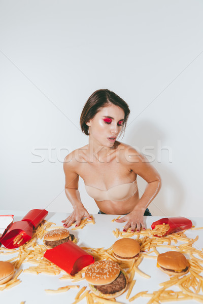Sensual young woman sitting at the table with fast food Stock photo © deandrobot