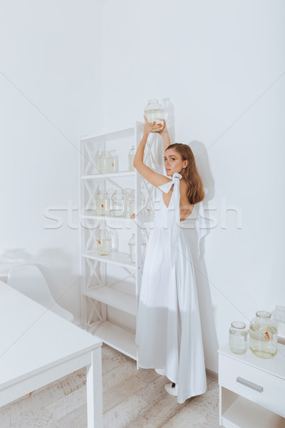 Woman standing and putting jar with gold fish on shelf Stock photo © deandrobot