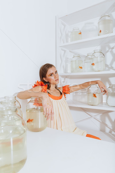 Woman sitting at the table with gold fishes in jars Stock photo © deandrobot
