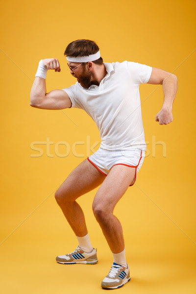 Vertical image of screaming sportsman in sunglasses showing bicep Stock photo © deandrobot