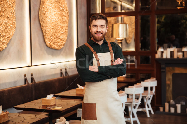 Amazing young man waiter standing in cafe. Stock photo © deandrobot