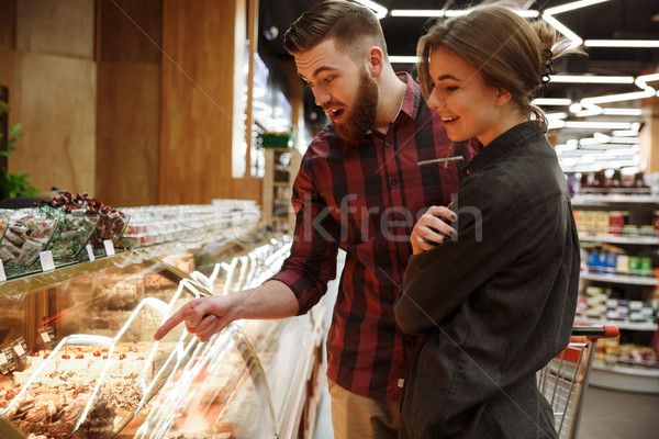 Young loving couple standing in supermarket choosing cake. Stock photo © deandrobot