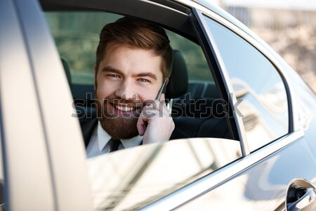 Image of Smiling Business man talking on phone Stock photo © deandrobot