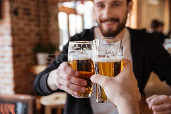 First view of man clinking glasses with friend Stock photo © deandrobot