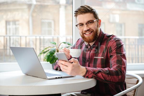 Foto stock: Homem · bonito · usando · laptop · computador · telefone · móvel · quadro · feliz